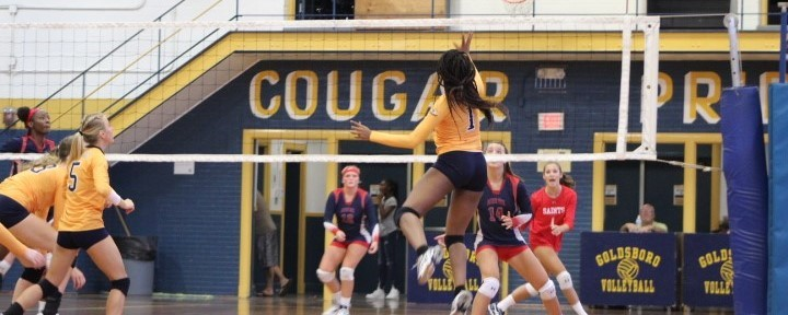 Goldsboro High School volleyball player hits ball over the net.